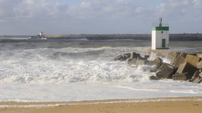 Big waves on a blocks jetty with a little lighthouse stock footage