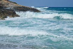Big waves in a rocky beach of Crete. Big waves of the blue sea captured from the coast in a beach of Crete Stock Photography