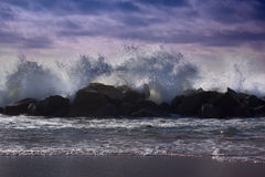Big waves breaking against the rocks. Waves breaking over the ro. Stormy ocean waves, beautiful seascape, big powerful tide in action, storm weather in a deep Stock Photos