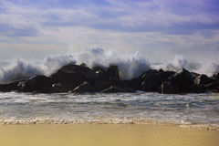 Big waves breaking against the rocks. Waves breaking over the ro Stock Photos