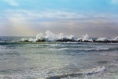 Big waves breaking against the rocks. Waves breaking over the ro. Stormy ocean waves, beautiful seascape, big powerful tide in action, storm weather in a deep Royalty Free Stock Images