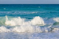Big waves hitting the beach in the Caribbeans. Big waves from the turquoise ocean, hitting the beach in the Caribbeans on a beautiful and sunny day Stock Photography