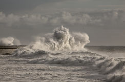 Big waves over Harbor wall Stock Photos
