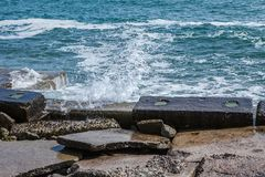 Big waves on rocky coast and blue sea Stock Images