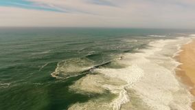 Big waves on sandy beach of the western coast of Portugal aerial stock video footage
