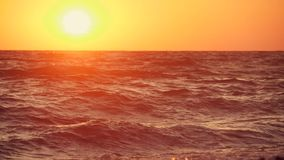 Big waves on a sea beach at sunset. Beautiful waves of slow motion video on the background of the orange sun