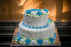 Big wedding cake with blue flowers. With interesting lighting Royalty Free Stock Photo