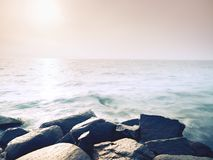 Big wet boulders in shore in smooth wavy sea. Stony coast defies to waves Stock Image
