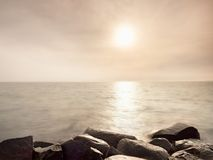 Big wet boulders in shore in smooth wavy sea. Stony coast defies to waves Royalty Free Stock Photos