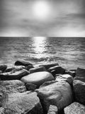 Big wet boulders in shore in smooth wavy sea. Stony coast defies to waves Royalty Free Stock Photo