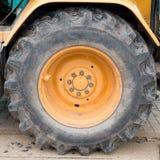 Big wheel on yellow tractor Stock Image