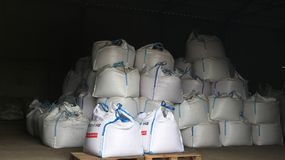Big white bags in the warehouse - products and fertilizers Royalty Free Stock Photo