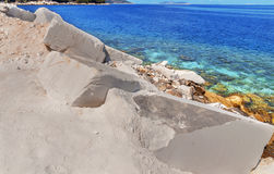 Big white blocks of raw marble and sea in Greece Stock Photos
