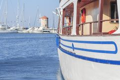 Big white boat side tied at dock with blue sea and lot small boat Stock Photos