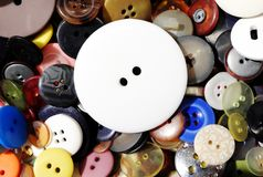 Big white button laying on other smaller colorful buttons royalty free stock photography