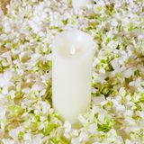 The big white candle in a wreath from artificial flowers. A wedd Royalty Free Stock Photos