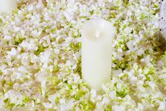 The big white candle in a wreath from artificial flowers. A wedd Stock Image