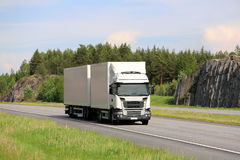 Big White Cargo Truck on Motorway. Big white cargo truck transports goods along motorway on a beautiful day of summer stock image