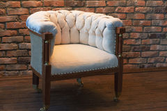 Big white chair on  brick wall background Stock Photo