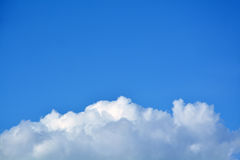 Big white cloud on blue sky. Bright blue skies with one huge cloud. Abstract background, space for text and design. Beautiful sky Stock Photos