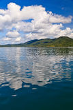 Big white clouds above a lake and mountains Royalty Free Stock Images
