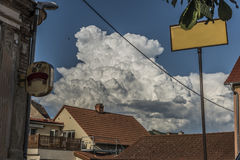 Big white clouds over roofs of Prackovice village stock images