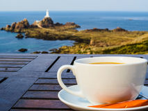 Big white cup on a table and seacoast as a background Royalty Free Stock Image