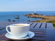 Big white cup on a table and seacoast and lighthouse as a background Stock Image