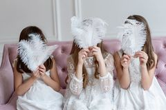 Big white feathers instead faces of girls in hands. Three girls have fun, having hidden the faces behind feathers royalty free stock images