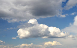 Big white fluffy clouds in the deep blue sky Stock Photos