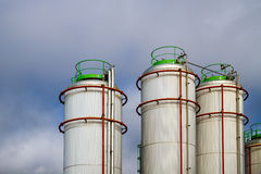 Big White gaz Storage Tanks. With red pipes against blue sky with some clouds Stock Photography