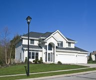 Big White House. A large white house with double garage and a retro street lamp Stock Photos
