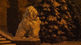 Big white lion statue covered by snow during snowfall. Snow-covered branches of trees during a heavy snow. Yellow light of street lamp stock video