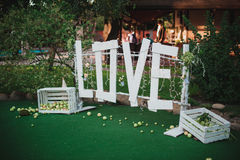 Big white love sign made of wood wedding decor. In garden royalty free stock photo