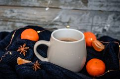 Big white mug with anise and tangerines on wooden gray background. Cozy winter home atmosphere royalty free stock photo