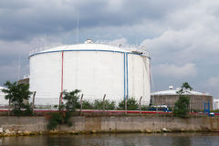Big white oil tank on the sea coast in port Stock Images