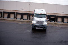Big white rig classic semi truck unloading in warehouse dock Stock Images