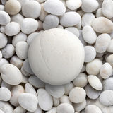 Big white rock laid on small round pebble, circle stone. White round shape of big sea stone laid on a pile of nature pebbles or a group of rocks. can use for royalty free stock photo