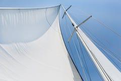 Big white sail hoisted. Genoa sail is hoisted on sailing boat mast Royalty Free Stock Image