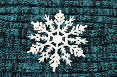 Big white snowflake on knitted wool background. Royalty Free Stock Image