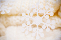 Big white snowflake on white knitted scarf background. Stock Image