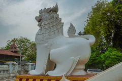 Big white statue of a lion at the entrance to a Buddhist temple in Mandalay. Myanmar royalty free stock photography