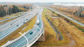 White truck rides on the highway among the flow of cars, aerial view