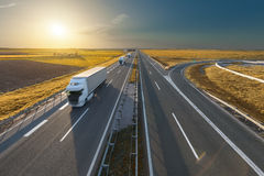 Big white trucks on the empty highway at sunset Royalty Free Stock Photography
