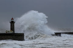 Big white wave over old lighthouse Stock Images
