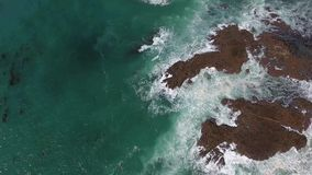 Big white waves in turquoise ocean water in stone shore coastline, top 4k aerial stock footage