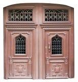 Big wide brown vintage wooden door with metal rusty lattices. Royalty Free Stock Photo