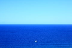Big blue ocean small white boat vastness stock image