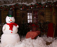 Big Winter Snowman on Decorated Wooden House Royalty Free Stock Photo
