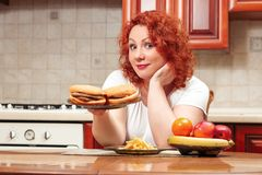 Big woman eat fast food. Red hair fat girl with burger, potato a. Nd fruit. Unhealthy food concept with plus size female on kitchen stock photography